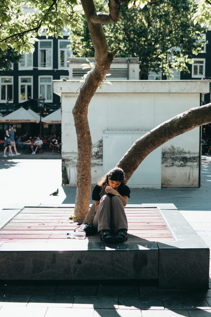 Girl reading a book under a tree on a summer afternoon