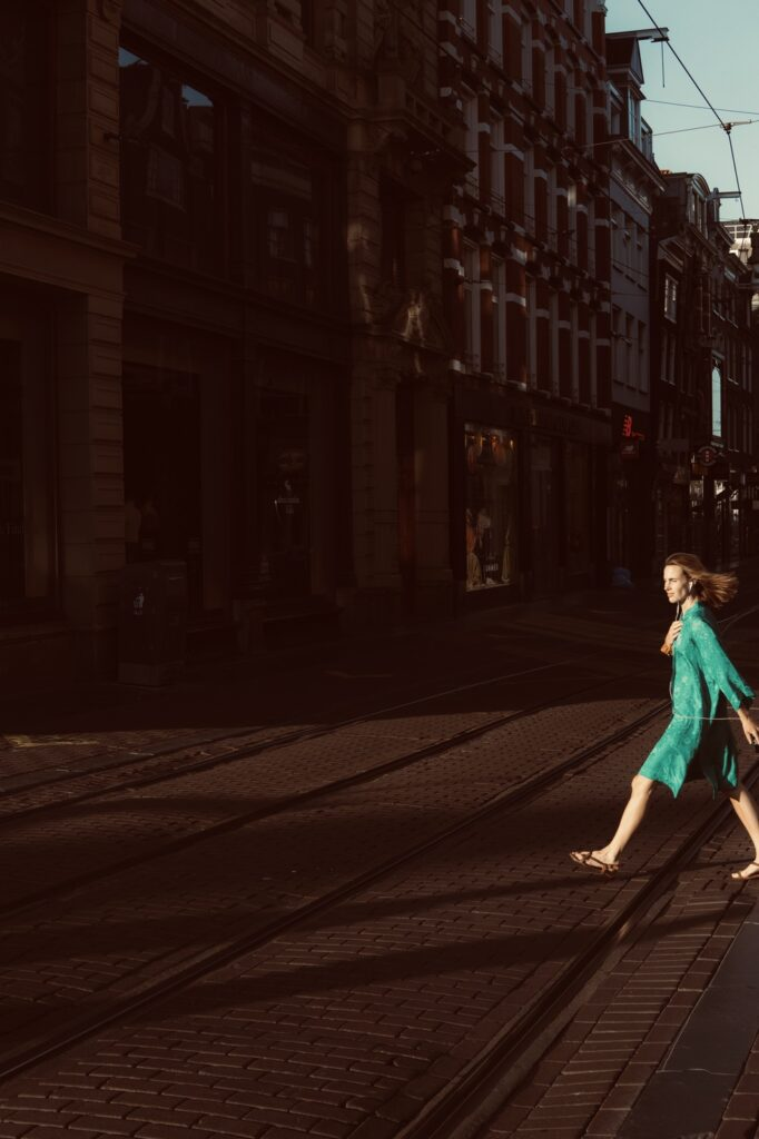 Leidsestraat, Amsterdam, woman happily marching in a green dress