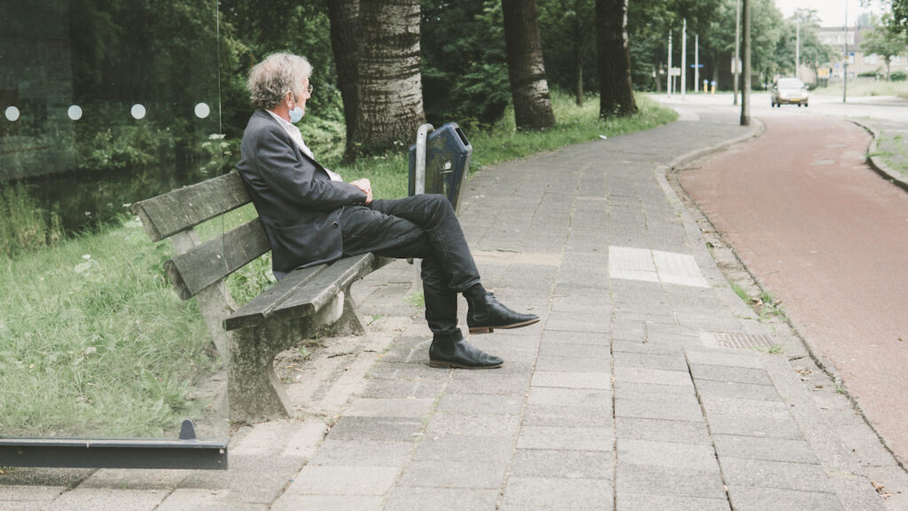 Man sitting on a bench with a mask on his chin