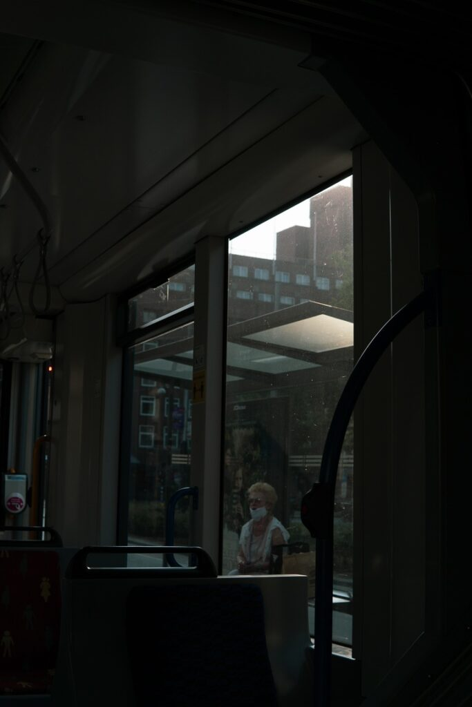 Woman with a face mask through a tram window