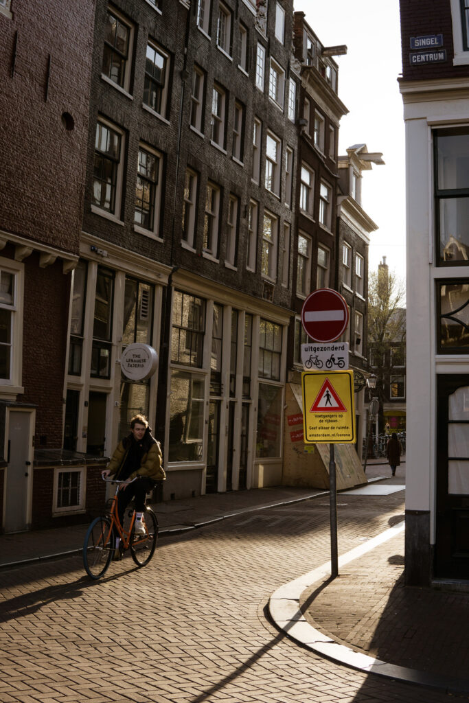 a biker cycling through the old part of Amsterdam