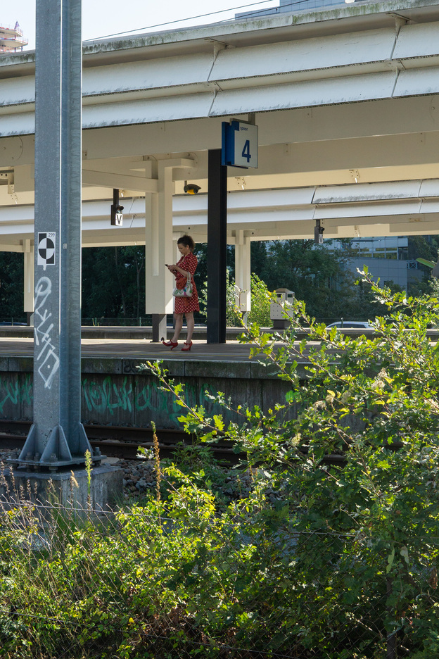 woman in a red dress waiting on a train