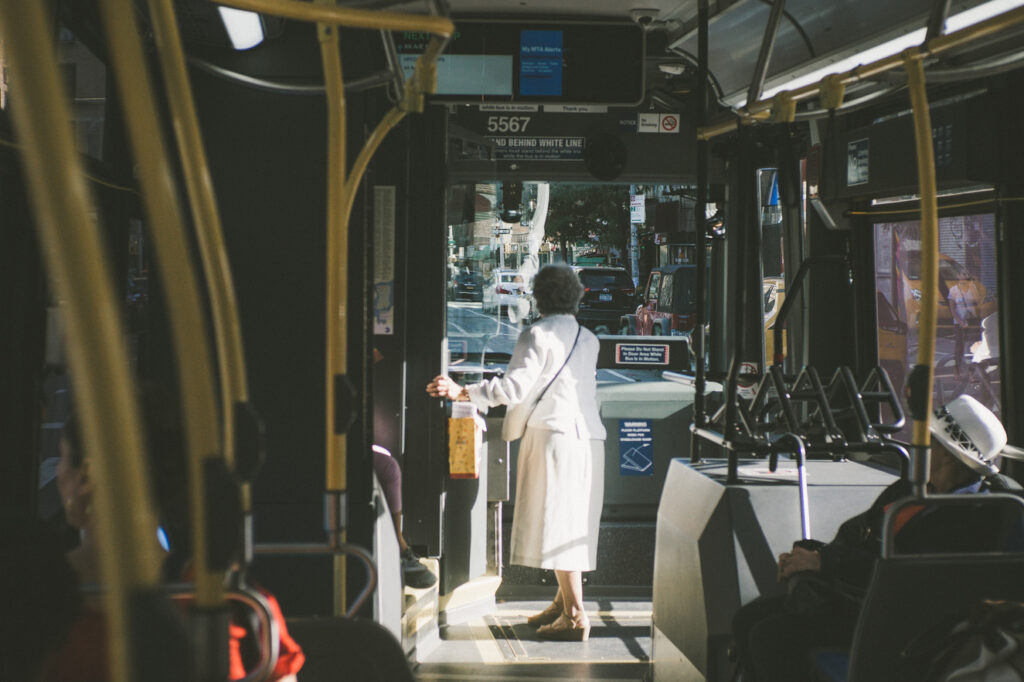elder lady on a bus wearing a white outfit