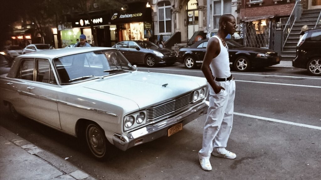 a guy dressed in white, posing in front of a Chevrolet Bel-Air
