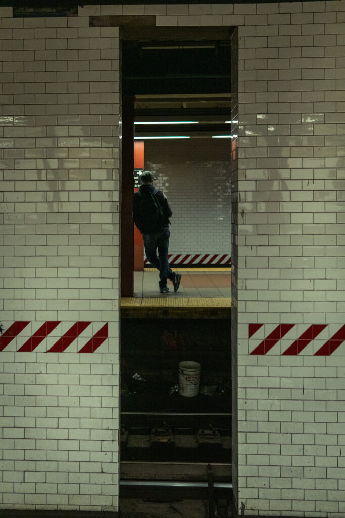 man leaning on a wall at the Canal subway station