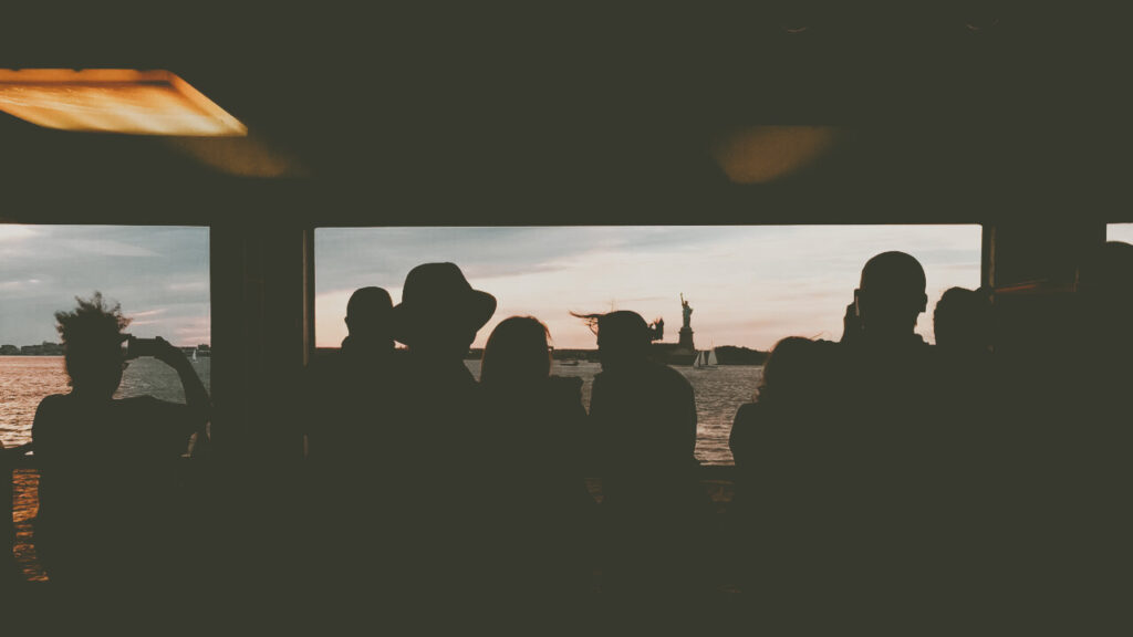 silhouettes on a ferry to the statue of liberty